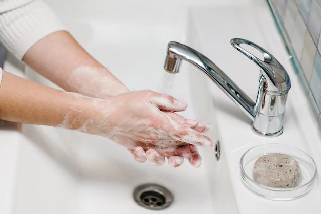 Mycie rąk. koronawirus profilaktyka. myć ręce mydłem antybakteryjnym i ciepłą bieżącą wodą, pocierając paznokcie i palce w zlewie. epidemiczny covid-19. zapobieganie chorobie grypowej.