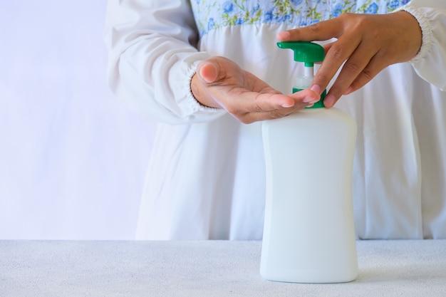 Mycie rąk mydłem w płynie lub żelem alkoholowym z butelki z pompką. zapobieganie i kontrola infekcji wirusem koronowym covid-19. koncepcja higieny i opieki zdrowotnej