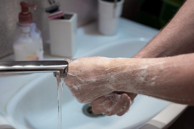 Mycie rąk mydłem w płynie w domu z bliska