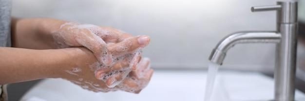 Mycie rąk pocieranie mydłem właściwą techniką pod umywalką w łazience w celu przeciwbakteryjnym zapobieganie epidemii koronawirusa (covid-19). zapobieganie chorobie grypowej.