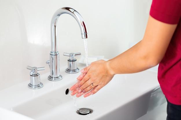Mycie rąk pod bieżącą wodą w umywalce z bliska. powiększ dłoń.