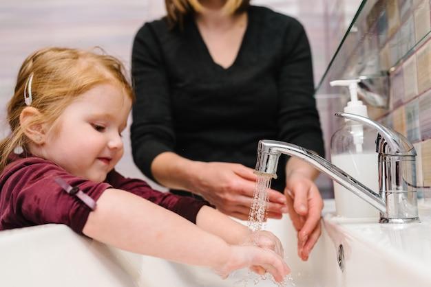 Mycie rąk. środki zapobiegawcze . mama mówi dziecku, jak prawidłowo myć ręce mydłem antybakteryjnym, ciepłą wodą ociera paznokcie i palce.