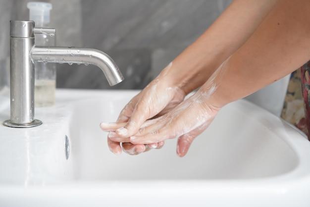 Mycie rąk w celu zapobiegania nowej chorobie koronawirusa 2019 lub covid-19. ludzie myją ręce przy zlewie w łazience, aby wyczyścić infekcję wirusową.