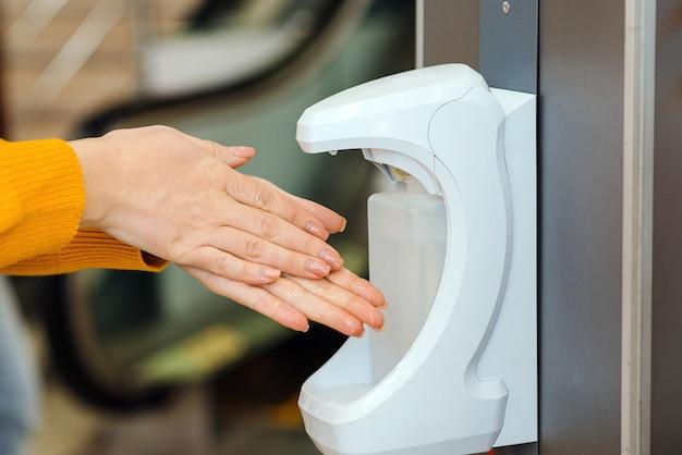 Mycie rąk za pomocą automatycznego dozownika środka odkażającego. automatyczny dozownik odkażający w supermarkecie. zapobieganie koronawirusom.