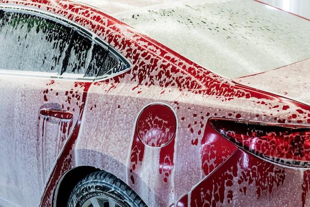 Mycie samochodu czerwonego aktywną pianą w myjni samochodowej.
