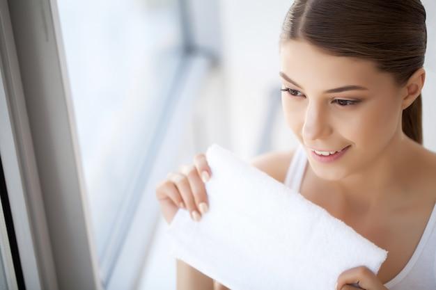 Mycie twarzy zbliżenie szczęśliwej kobiety susząca skóra z ręcznikiem. wysoka rozdzielczość