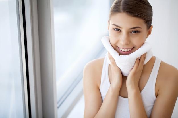 Mycie twarzy. zbliżenie szczęśliwej kobiety suszarnicza skóra z ręcznikiem. wysoka rozdzielczość
