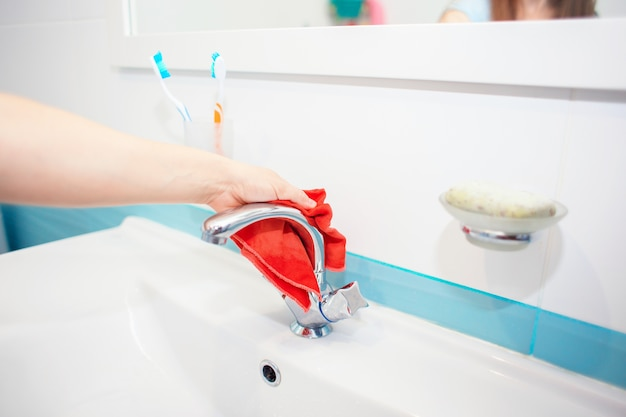 Mycie umywalki i kranu w łazience. dezynfekcja w domu. porządkowanie domu. wiosenne porządki. czyszczenie toalet. czyszczenie zlewu szmatką