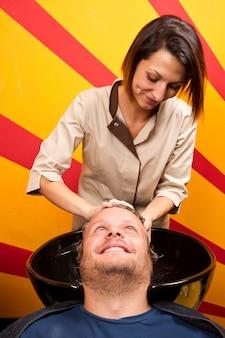Mycie włosów człowieka w salonie fryzjerskim salonu piękności