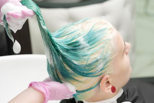 Mycie zielonego koloru włosów młodej kobiety szamponem w zlewie pracującym fryzjerem w różowym ochronnym ...