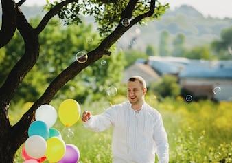 Mydlane balony latają wokoło mężczyzna pozyci pod zielonym drzewem
