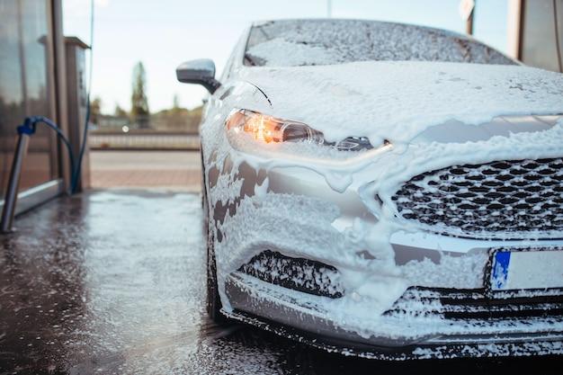 Mydlany szary sedan stoi w samoobsługowej myjni samochodowej