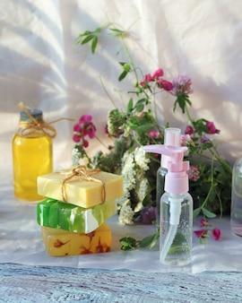 Mydło, spray, bukiet ziół leczniczych i szklane butelki z aromatycznym olejkiem na drewnianym stole