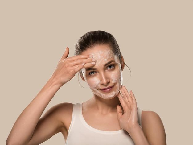 Mydło twarz kobiety czyste piękno skóry. kolor tła. brązowy