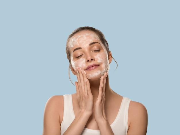 Mydło twarz kobiety czyste piękno skóry. kolor tła. niebieski.