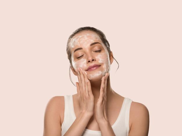 Mydło twarz kobiety czyste piękno skóry. kolor tła. różowy