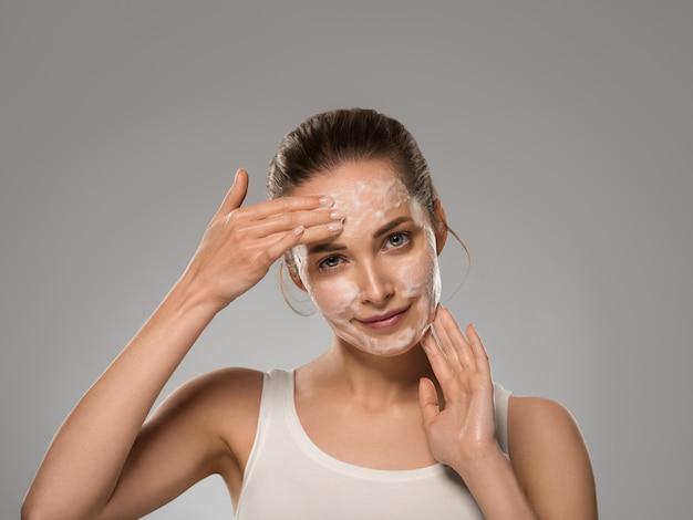 Mydło twarz kobiety czyste piękno skóry. kolor tła. szary
