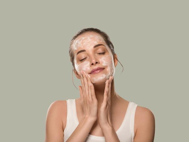 Mydło twarz kobiety czyste piękno skóry. kolor tła. zielony