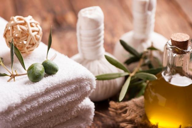 Mydło z oliwy z oliwek i ręcznik kąpielowy na drewnianym stole