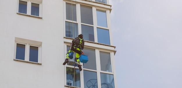 Myjka do szyb mycie elewacji budynku. osoba czyszcząca okno budynku. kopiuj przestrzeń