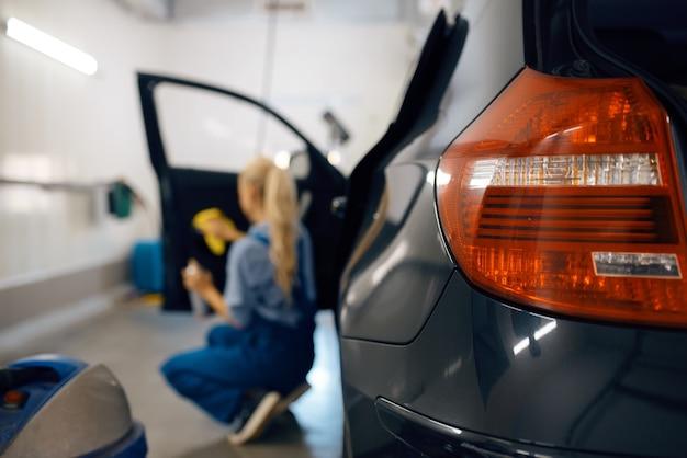 Myjka żeńska z gąbką czyści tapicerkę drzwi samochodowych, myjnia samochodowa. kobieta myje samochód, myjnię samochodową, myjnię samochodową
