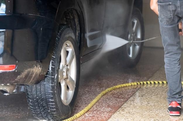 Myjnia samochodowa. czyszczenie samochodu wodą pod wysokim ciśnieniem i pianą. transport