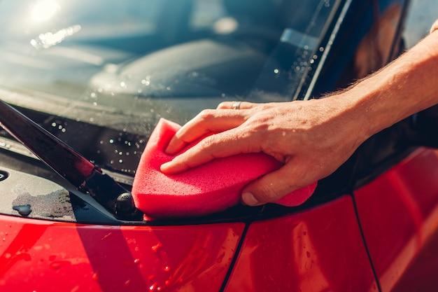 Myjnia samochodowa. mężczyzna czyści samochód z mydlaną gąbką outdoors. zbliżenie