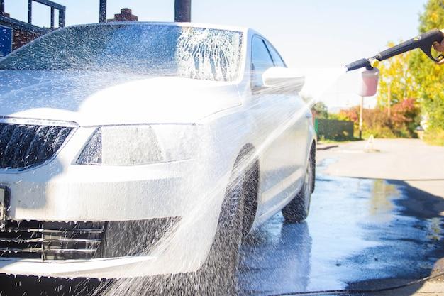 Myjnia samochodowa. myjnia samochodowa. człowiek myje samochód. pianka