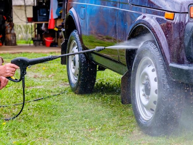 Myjnia samochodowa po południu na świeżym powietrzu z aparatem wysokociśnieniowym. silny strumień wody zmyje brud z fioletowej karoserii samochodu, ze szkła, felg i opon.