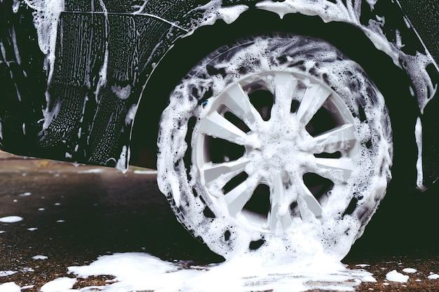 Myjnia samochodowa z aktywnym mydłem w pianie. czyszczenie opony koła. koncepcja usługi sprzątania komercyjnego.