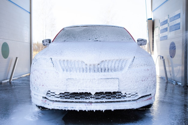 Myjnia samochodowa z mydłem i wodą pod wysokim ciśnieniem. maszyna jest całkowicie mydlana