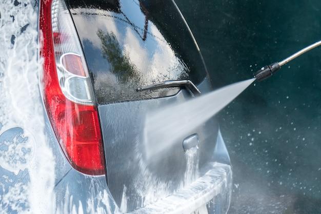 Myjnia samochodowa zbliżenie. mycie samochodu wodą pod wysokim ciśnieniem.