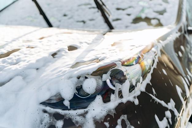 Myjnia zewnętrzna z mydłem w piance. czarne auto myte wodą i mydłem pod wysokim ciśnieniem w myjni samochodowej. koncepcja usługi sprzątania. samoobsługowa myjnia samochodowa