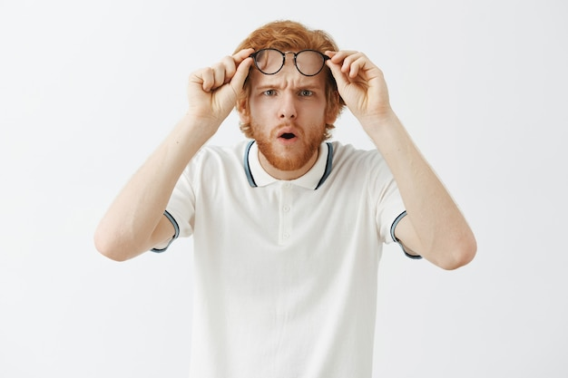 Mylić brodaty rudy facet pozuje przy białej ścianie w okularach