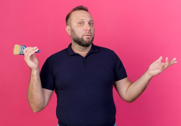 Mylić dorosły mężczyzna słowiański trzymając pędzel i pokazując puste ręce na białym tle