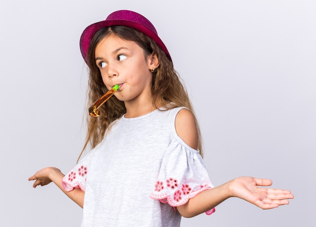 Mylić dziewczynka kaukaski z fioletowym kapeluszem strony dmuchanie gwizdkiem strony patrząc na bok na białym tle na białej ścianie z miejsca na kopię