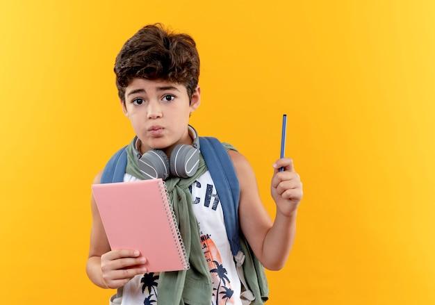 Mylić mały chłopiec w szkole noszenie plecaka i słuchawki trzymając notebook z piórem na białym tle na żółtym tle