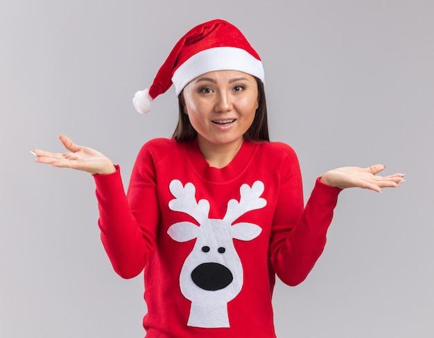Mylić młoda azjatycka dziewczyna ubrana w świąteczny kapelusz z swetrem, rozkładając ręce na białym tle