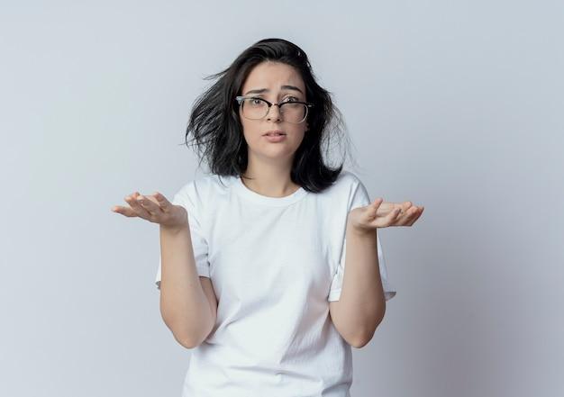 Mylić młoda dziewczyna całkiem kaukaski w okularach pokazując puste ręce patrząc na kamery na białym tle na białym tle z miejsca kopiowania