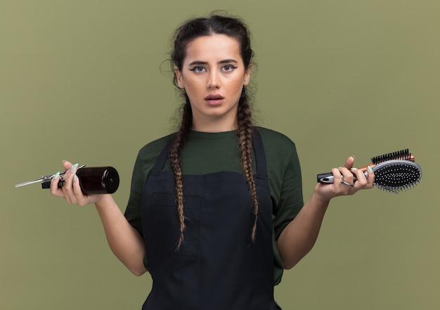 Mylić młoda kobieta fryzjer w mundurze trzymając narzędzia fryzjerskie na białym tle na oliwkowej ścianie