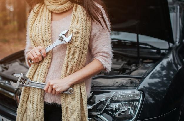 Mylić młoda kobieta, patrząc na uszkodzony silnik samochodu na ulicy trzyma klucz
