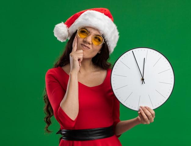 Mylić młoda ładna dziewczyna ubrana w santa hat i okulary trzyma zegar patrząc w górę trzymając rękę na brodzie na białym tle na zielonym tle