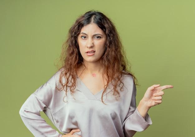 Mylić młoda ładna kobieta pracownik biurowy wskazuje na bok i kładąc rękę na biodrze