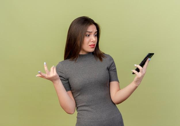 Mylić młoda ładna kobieta trzymając telefon komórkowy i patrząc na niego i pokazując pustą rękę na białym tle na oliwkowym tle
