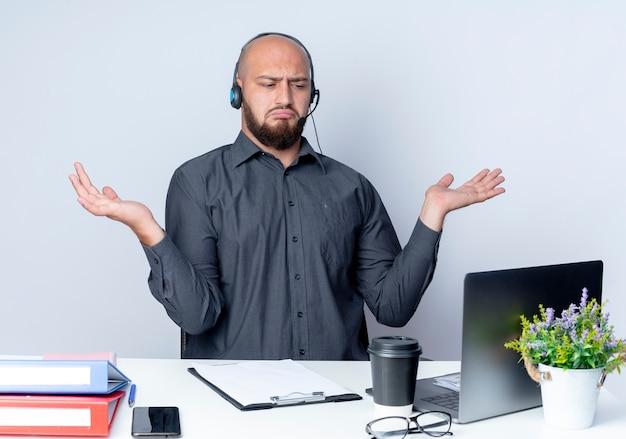 Mylić młody łysy mężczyzna call center sobie zestaw słuchawkowy siedzi przy biurku z narzędzi pracy patrząc na laptopa i pokazując puste ręce na białym tle