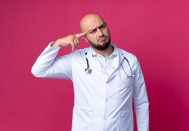 Mylić młody mężczyzna łysy lekarz ubrany w szlafrok i stetoskop, kładąc palec na czole na białym tle na różowej ścianie