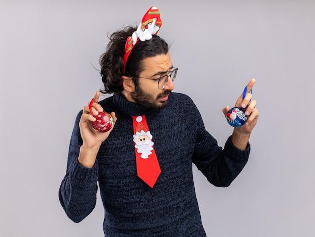 Mylić młody przystojny facet ubrany w świąteczny krawat z obręcz do włosów, trzymając i patrząc na bombki na białym tle