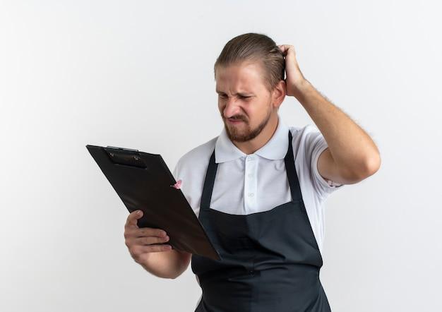 Mylić młody przystojny fryzjer na sobie mundur trzymając i patrząc na schowek ręką na głowie na białym tle
