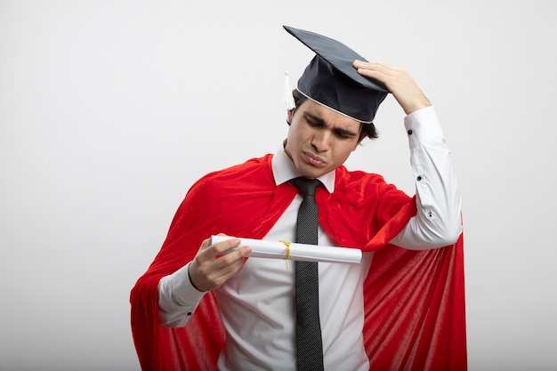 Mylić młody superbohater facet sobie krawat i absolwent kapelusz trzymając i patrząc na dyplom, kładąc rękę na kapelusz na białym tle