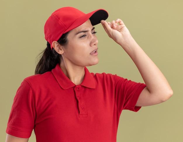 Mylić patrząc na bok młoda dziewczyna dostawy ubrana w mundur z czapką trzymając czapkę na białym tle na oliwkowej ścianie